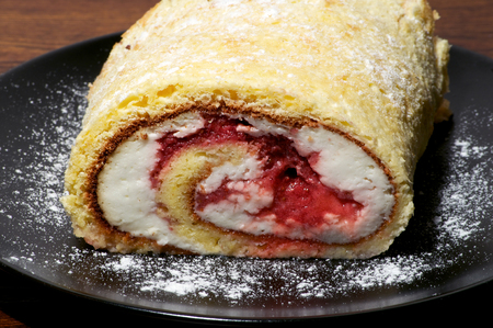 Rolled pie on the plate over wooden background macro