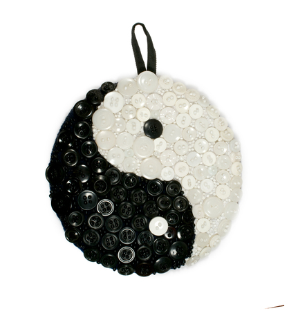 fengshui: Yin and yang sign made out of buttons over wooden background