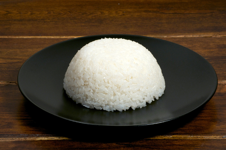 rice plate: Portion of rice on the black plate on the wooden table Stock Photo