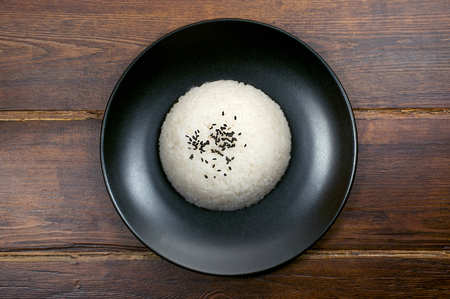 mouthwatering: Portion of rice on the black plate top view with sesame