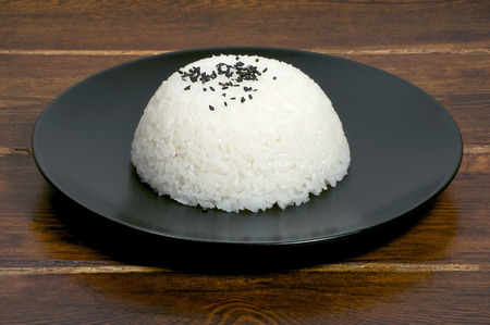 side plate: Portion of rice on the black plate side view with sesame