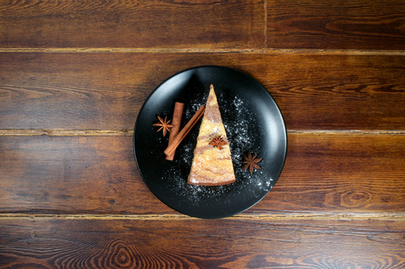 mouthwatering: Piece of cake on plate in the center over wooden table