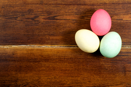 dark pastel green: Three easter eggs over wooden background with card Stock Photo