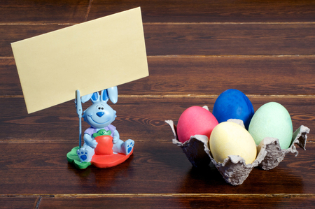 cardholder: Colorful easter eggs in stand with bunny with greeting card over wooden background