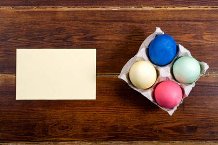 dark pastel green: Various easter egg over wooden background with card from top