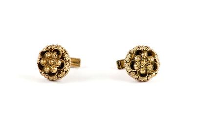 bibelot: Isolated close up of golden flower cufflinks over white
