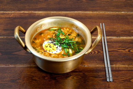 Korean ramen with egg and green onion on golden pan Stock Photo