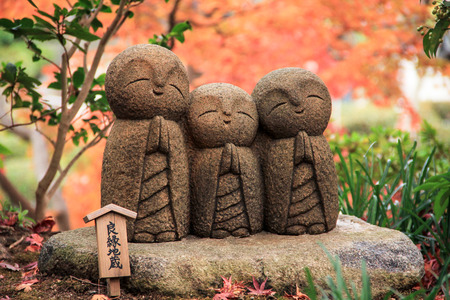 supposed: Three little monk rock carving statue with autumn leaves. Japanese word in small wood plate is Ryouen-Jizo which supposed to bring a good match and hope you have the good fortune. Stock Photo