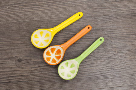 baby cutlery: Spoons of different colors on wood background