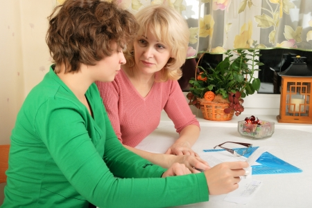 age 50 55 years: Adult blond woman and young woman discussing documents Stock Photo