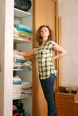 closet door: young woman near sliding-door wardrobe with bed linen Stock Photo