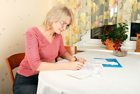 50 55: Adult blond woman signing documents Stock Photo