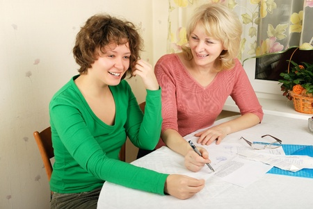 age 50 55 years: Adult blond woman and young woman signing documents Stock Photo