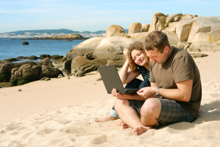 man and woman working with computer at beach photo