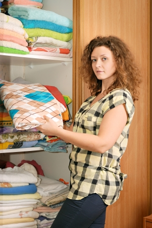 young woman near sliding-door wardrobe with bed linen photo