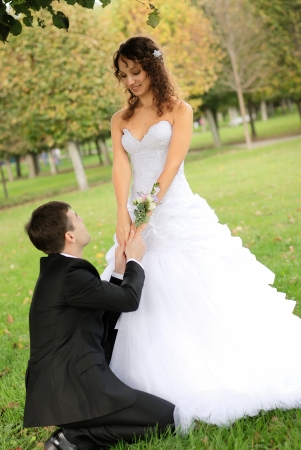 young bride and the bridegroom in the park photo
