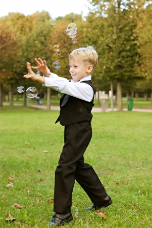 only 1 boy: young boy playing with soap bubbles Stock Photo