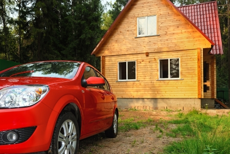 Modern wooden Russian traditional house and the car of the red colour photo