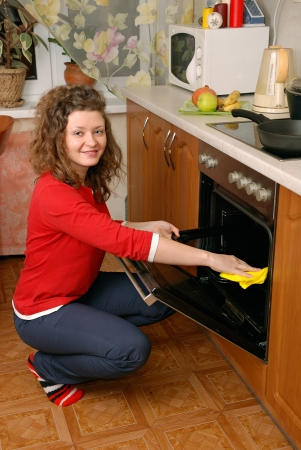 woman cleaning contemporary kitchen oven photo