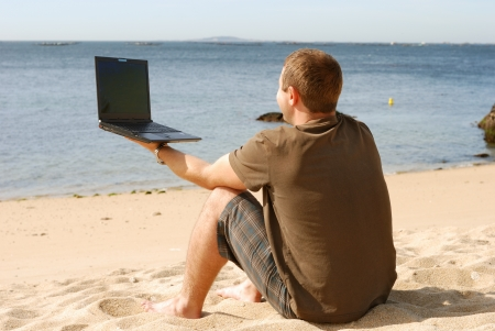 man working with computer at beach photo