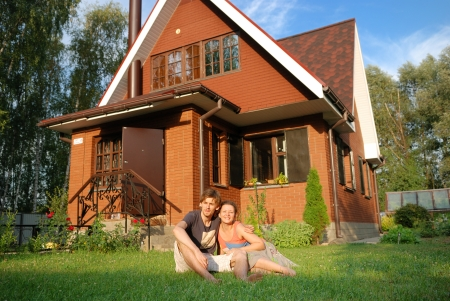 russian man: young pair sitting near new their house Stock Photo
