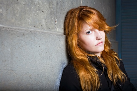 Scared and lonely, moody portrait of a beautiful fashoinable young redhead girl. photo