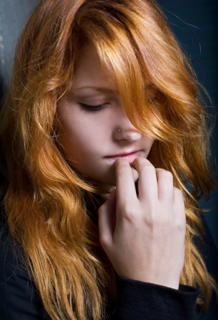 cool down: Moody dark portrait of a young redhead girl with contemplative expression.