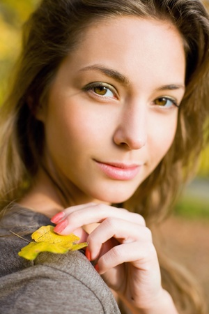 Beautiful young brunette posing in the park at fall. photo