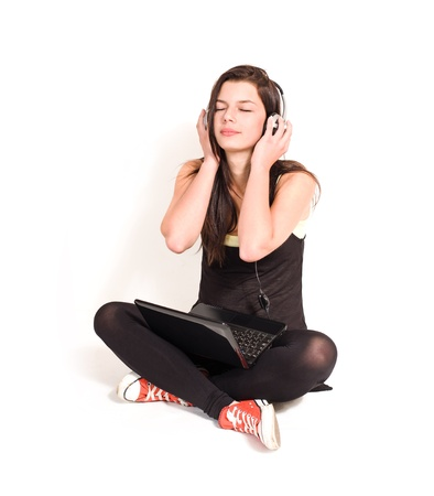 Gorgeous young brunette listening to music using small black laptop. photo