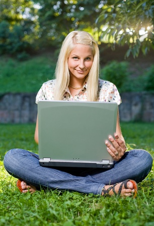 Pretty young blond girl using laptop in sunlit green park. Stock Photo - 9311404