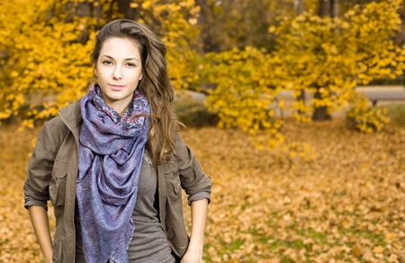 Beautiful young brunette posing  in sunlit autumn park. Stock Photo - 9310890