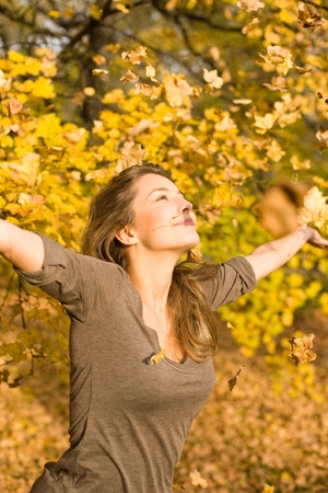 Beautiful young brunette among falling leaves Stock Photo - 9311221