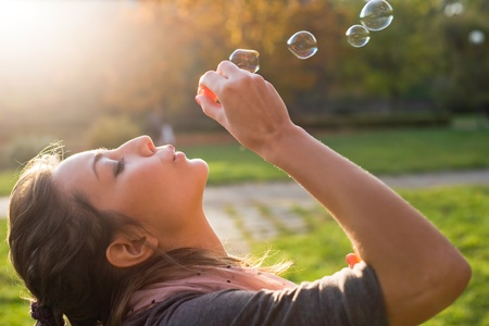 by blowing: Beautiful yopung brunette girl blowing soap bubbles into the wind. Stock Photo