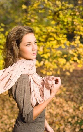 Gorgeous young brunette strolling in autumn park. photo
