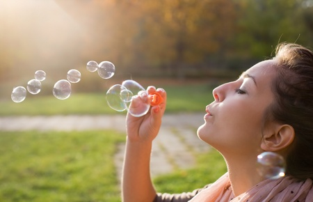 Beautiful yopung brunette girl blowing soap bubbles into the wind. Stock Photo
