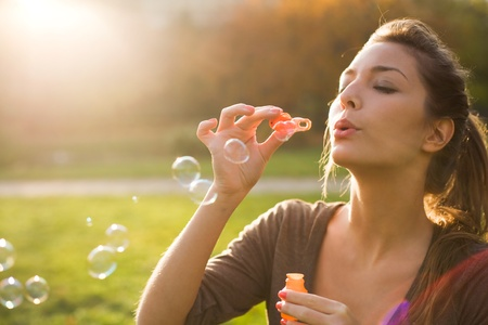 relaxed woman: Blowin bubbles into the sun. Stock Photo