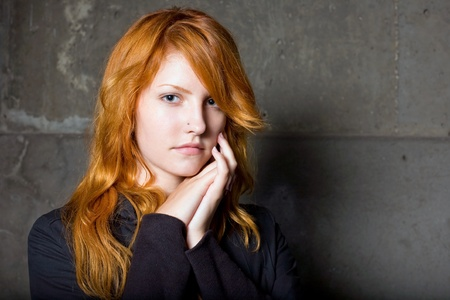 Moody portrait of a beautiful fashoinable young redhead girl with sad facial expression. photo