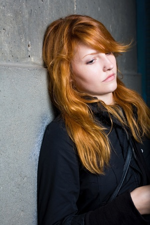 portait: Sadness - moody portrait of a beautiful young redhead girl. Stock Photo