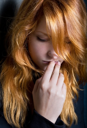 Moody dark portrait of a young redhead girl with contemplative expression. photo