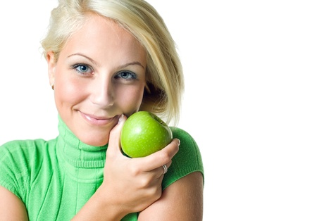 Beautiful young blonde girl hodinga green apple smiling at the camera, isolated on white background. photo