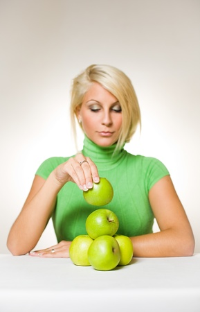 turtleneck: Portrait of beautiful fit young blond assembling an apple pyramid.