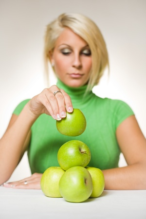 Portrait of beautiful fit young blond assembling an apple pyramid. photo