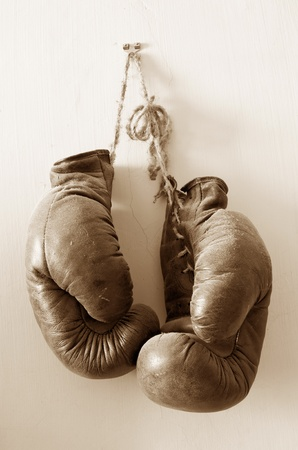 boxing glove: hang up the gloves, old worn leather boxing gloves in sepia tones, hanged up on grunde style wall, lots of dust.