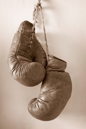 hang up: hang up the gloves, old worn leather boxing gloves in sepia tones, hanging on grunge style wall. Stock Photo