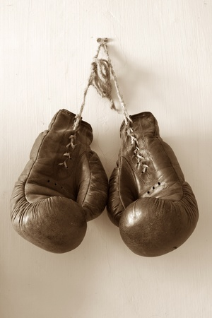 leather glove: hang up the gloves, old worn leather boxing gloves in sepia tones, hanged up on grunde style wall.