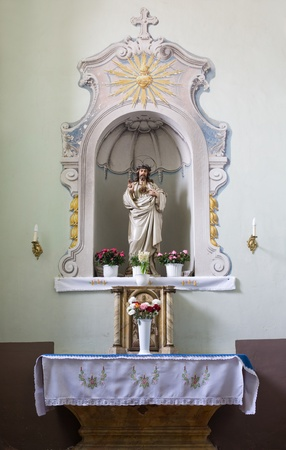 Church interior, small altar with sculpture of Jesus Christ and flowers. Stock Photo - 9328751