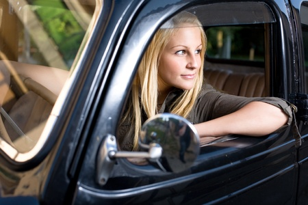 Beautiful young blond girl in a black vintage car, looking away. photo