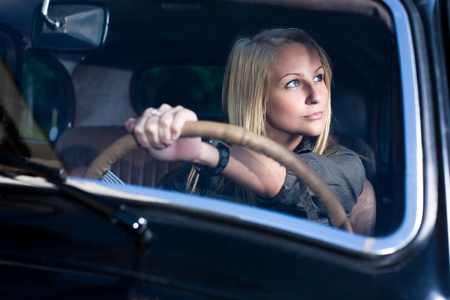 Beautiful young blond girl smiling in a black vintage car, holding the streering wheel, shot through the windscreen. photo