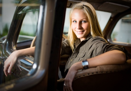 Beautiful young blond girl smiling in a black vintage car, looking back over the shoulder. photo