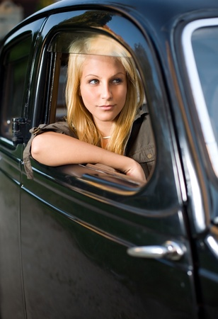 Beautiful young blond girl looking out the window of a black vintage car. photo